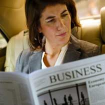 female executive reading newspaper back of limousine
