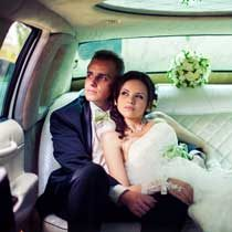 wedding couple in back of limousine